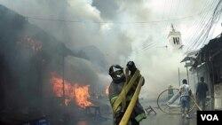 Seorang pemadam kebakaran melepaskan selang untuk memadamkan api di Tegucigalpa, Honduras (18/2).