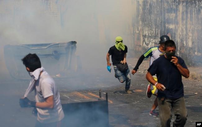 Người biểu tình tháo chạy tránh hơi cay của binh lính của lực lượng Vệ binh Quốc gia ở Urena, Venezuela, gần biên giới với Colombia, ngày 23 tháng 2, 2019.