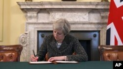 Britain's Prime Minister Theresa May signs the official letter to European Council President Donald Tusk, in 10 Downing Street, London, Tuesday March 28, 2017, invoking Article 50 of the bloc's key treaty.