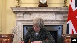 PM INggris Theresa May menandatangani surat resmi untuk pemimpin Dewan Uni Eropa, Presiden Donald Tusk, untuk pengunduran diri Inggris dari keanggotaan Uni Eropa, di ruang kerjanya di 10 Downing Street, London, 28 Maret 2017. (Christopher Furlong/Pool Photo via AP)
