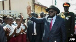South Sudan President Salva Kiir waves as he greets schoolchildren at Juba International Airport in Juba on Sept. 13, 2018, after returning from the Ethiopian capital Addis Ababa where the latest peace agreement with opposition leader Riek Machar was finalized.