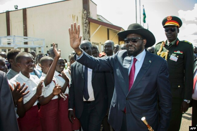 South Sudan President Salva Kiir waves as he greets schoolchildren at Juba International Airport in Juba on Sept. 13, 2018, after returning from the Ethiopian capital Addis Ababa where the latest peace agreement with opposition leader Riek Machar was signed.