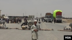 FILE - A boy stands at the closed Chaman border crossing between Pakistan and Afghanistan with trucks seen stranded in the background.