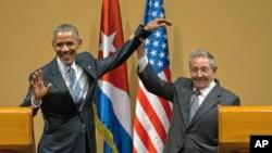 Tư liệu- Chủ tịch Cuba Raul Castro nâng cánh tay của Tổng thống Hoa Kỳ Barack Obama trong một cuộc họp báo chung.