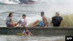 Residents along Manila Bay play in the waves created by nearby Typhoon Noul as it approaches the northern Philippines, May 10, 2015.