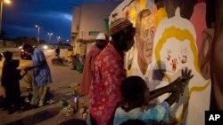 2013年6月25日,壁畫藝術家索萊耶(中)繪製歡迎美國總統奧巴馬來訪的壁畫並讓一名兒童在壁畫上印上小手印。