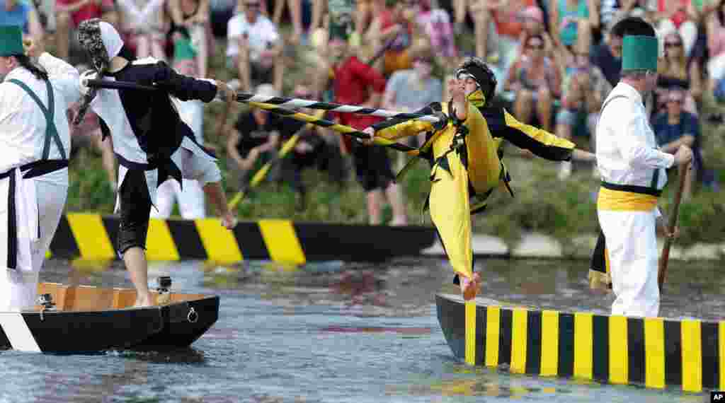 Two men fight with their lances at the traditional fishermen's joust tournament on river Danube in Ulm, southern Germany. The jousting contest with 16 jousting pairs in historic costumes represents historical figures and original characters of the city of Ulm.