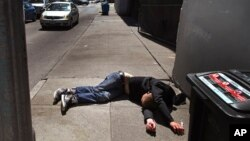 FILE - In this April 26, 2018, file photo, a man lies on the sidewalk beside a recyclable container in San Francisco, California. A record 621 people died of drug overdoses in San Francisco so far this year, a number far higher than the 173 deaths from CO