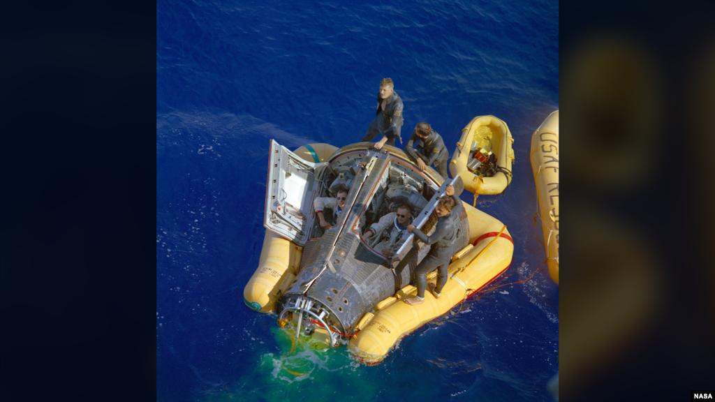 17 марта 1966 года самая сложная часть миссии «Джемини-8» для Нила Армстронга уже была позади. На этом снимке мы видим, как Дэвид Скотт (слева) и Нил Армстронг (справа) дожидаются прибытия судна, которое сможет доставить их к побережью. Миссия оказалась успешной. Скотт и Армстронг смогли осуществить первую в истории стыковку двух космических кораблей («Джемини-8» состыковался с ракетой-целью «Аджена»). Однако полет чуть было не обернулся трагедией: во время стыковки двигатель мишени неожиданно включился, из-за чего связка двух аппаратов начала вращаться. Экипаж был вынужден отстыковаться от «Аджены», что только увеличило вращение корабля. Пытаясь бороться с колоссальными перегрузками и находясь на грани потери сознания, Армстронг успел включить ручное управление посадочных двигателей и погасить вращение.