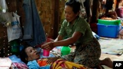A family member takes care of a HIV patient at a HIV/AIDS care center outside Yangon, Myanmar, February 2015. The World Health Organization estimates that 39 million people died from the virus. (AP Photo/Khin Maung Win)