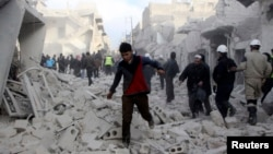 People run on debris at a site hit by what activists said was an airstrike by forces loyal to Syria's President Bashar al-Assad in Aleppo, December 18, 2013.
