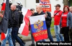 Almanya'nın Duisburg kentinde yürüyen bir neonazi gösterici, elinde Rusya bayrağıyla