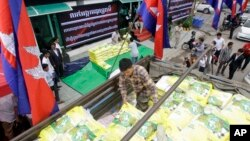 A worker unloads sacks of rice from a truck during a campaign organized by a private company for selling lower price of rice, in Phnom Penh, Cambodia, Saturday, Sept. 24, 2016. Cambodian farmers in northwestern Battambang province, recently piled up a hun