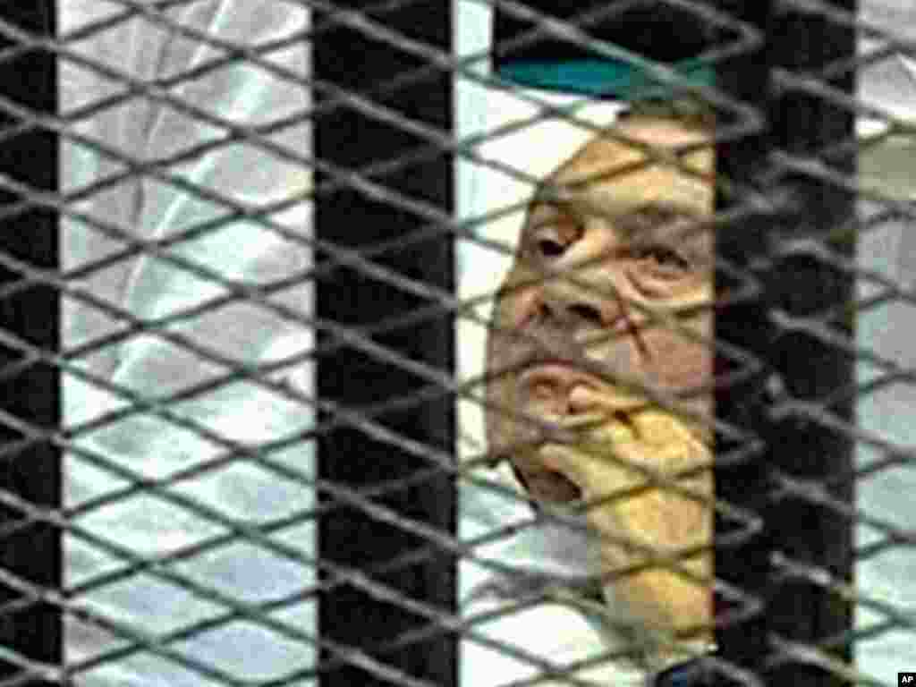 On August 3, 2011, Hosni Mubarak is in a Cairo courtroom lying on a hospital bed inside a cage of mesh and iron bars as his trial began. (AP/Egyptian State TV)