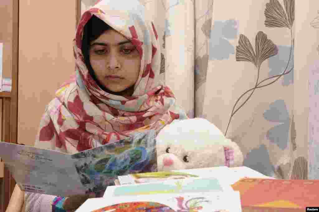 ໃນຮູບທີ່ນໍາອອກເຜີຍແຜ່ໃນວັນທີ 8 ພະຈິກ, 2012, ນາງ Malala Yousafzai ອ່ານບັດອວຍພອນ ໃນຂະນະທີ່ກໍາລັງຟື້ນຕົວຈາກການໄດ້ຮັບບາດເຈັບ ຢູ່ໂຮງໝໍ ພະລາຊີນີ Elizabeth ໃນເມືອງ Birmingham, ປະເທດອັງກິດ.