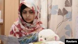 Nữ sinh Pakistan Malala Yousufzai đọc một tấm thiệp trong lúc đang được điều trị tại Bệnh viện The Queen Elizabeth ở Birmingham, Anh (ảnh của Reuters đăng ngày 8/11/2012)