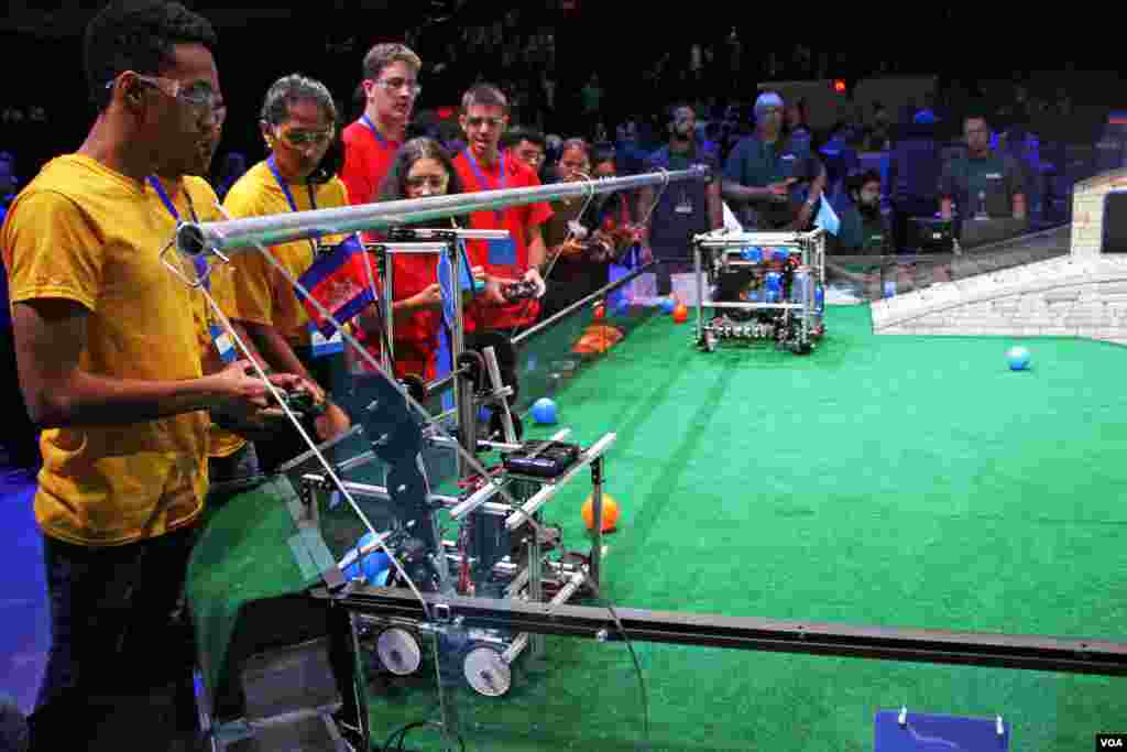 The robot of the Cambodian team tries to catch a ball the in front of the Guyana team (left, yellow), during First Global Challenge robotics competition in Washington, DC, Monday, July 17, 2017. (Nem Sopheakpanha/VOA Khmer)