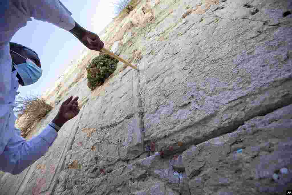 A worker removes prayer notes left by visitors in gaps between stones at the Western Wall, the holiest site where Jews can pray in Jerusalem's old city, ahead of Rosh Hashana, the Jewish new year. The notes are buried in a nearby cemetery.
