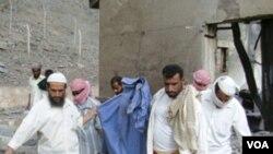 Warga setempat membawa anggota tubuh seorang korban tewas yang ditemukan di dalam pabrik amunisi di Jaar, Senin (28/3).