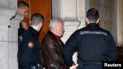"""FILE - Ilich Ramirez Sanchez, known as """"Carlos the Jackal,"""" is surrounded by French gendarmes as he leaves the Paris courthouse, March 3, 2014."""