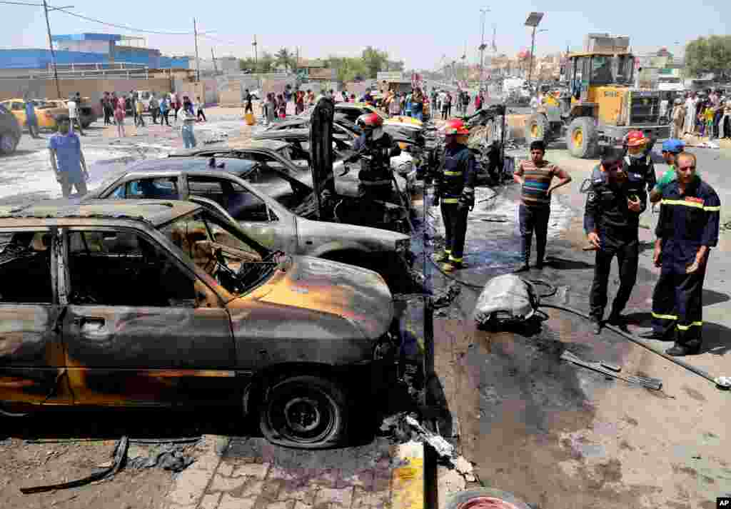 Firefighters extinguish vehicles after a car bomb explosion in the Shi'ite stronghold of Sadr City, Baghdad, May 13, 2014.