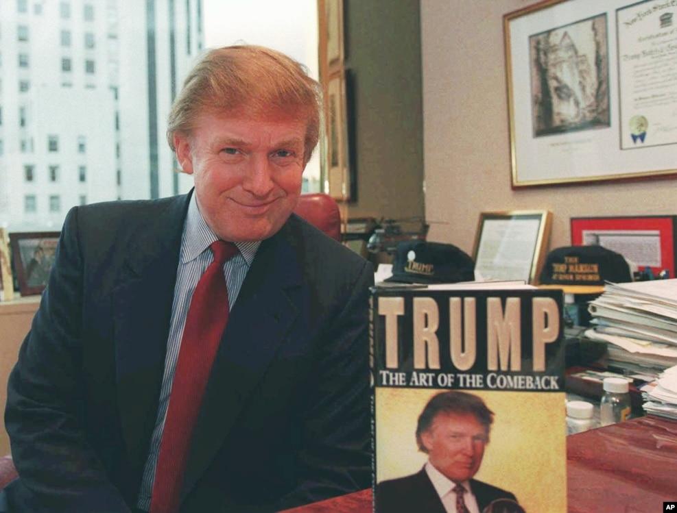 1997年11月7日,川普在他的位於紐約曼哈頓的辦公室裡,和他寫的第三本書《川普:回歸的藝術》( Trump: The Art of the Comeback )合影,這本書曾經是《紐約時報》評出的最佳書籍和最暢銷書籍的第一名。
