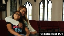Nury Chavarria, 43, poses with her 9-year-old daughter, Hayley inside Iglesia De Dios Pentecostal church in New Haven, Conn., on Monday, July 24, 2017