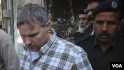 Polisi dan petugas pengadilan Lahore mengawal diplomat AS, Raymond Davis, keluar dari ruang persidangan setelah Davis menghadap hakim (1/28).