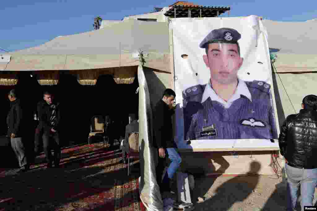 Relatives of Islamic State captive Jordanian pilot Muath al-Kasaesbeh place a poster of him in front of their new gathering headquarters in Amman. Japan and Jordan worked hard Friday to find out what had happened to two of their nationals being held by IS, after a deadline passed for the release of a would-be suicide bomber being held on death row in Amman.