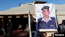 Relatives of Islamic State captive Jordanian pilot Muath al-Kasaesbeh place a poster of him in front of their new gathering headquarters in Amman, Jan. 30, 2015.