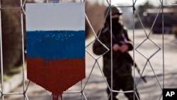 FILE - The former emblem of the Ukrainian army is covered in paint in the colors of Russia's flag as a masked soldier is seen behind a gate to a military base in Simferopol, Crimea, March 13, 2014.