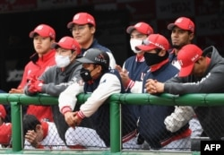 SK Wyverns players wearing face masks watch the game from the dugout during the opening game against Hanwha Eagles for South Korea's new baseball season at Munhak Baseball Stadium in Incheon on May 5, 2020.