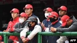 Para pemain SK Wyvern mengenakan masker, menonton pertandingan dari ruang istirahat selama pertandingan pembukaan melawan Hanwha Eagles untuk musim baseball Korea Selatan yang baru di Munhak Baseball Stadium di Incheon pada 5 Mei 2020.