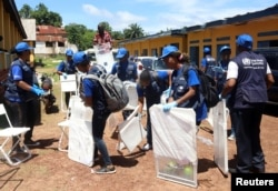 World Health Organization (WHO) workers prepare a center for vaccination during the launch of a campaign aimed at beating an outbreak of Ebola in the port city of Mbandaka, Democratic Republic of Congo, May 21, 2018.