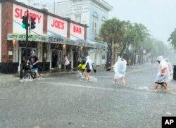 Pengunjung berjalan menuju Sloppy Joe's Bar, melintasi Duval Street yang banjir akibat angin kencang dan hujan melewati Key West, Florida, Selasa, 6 Juli 2021. (AP)