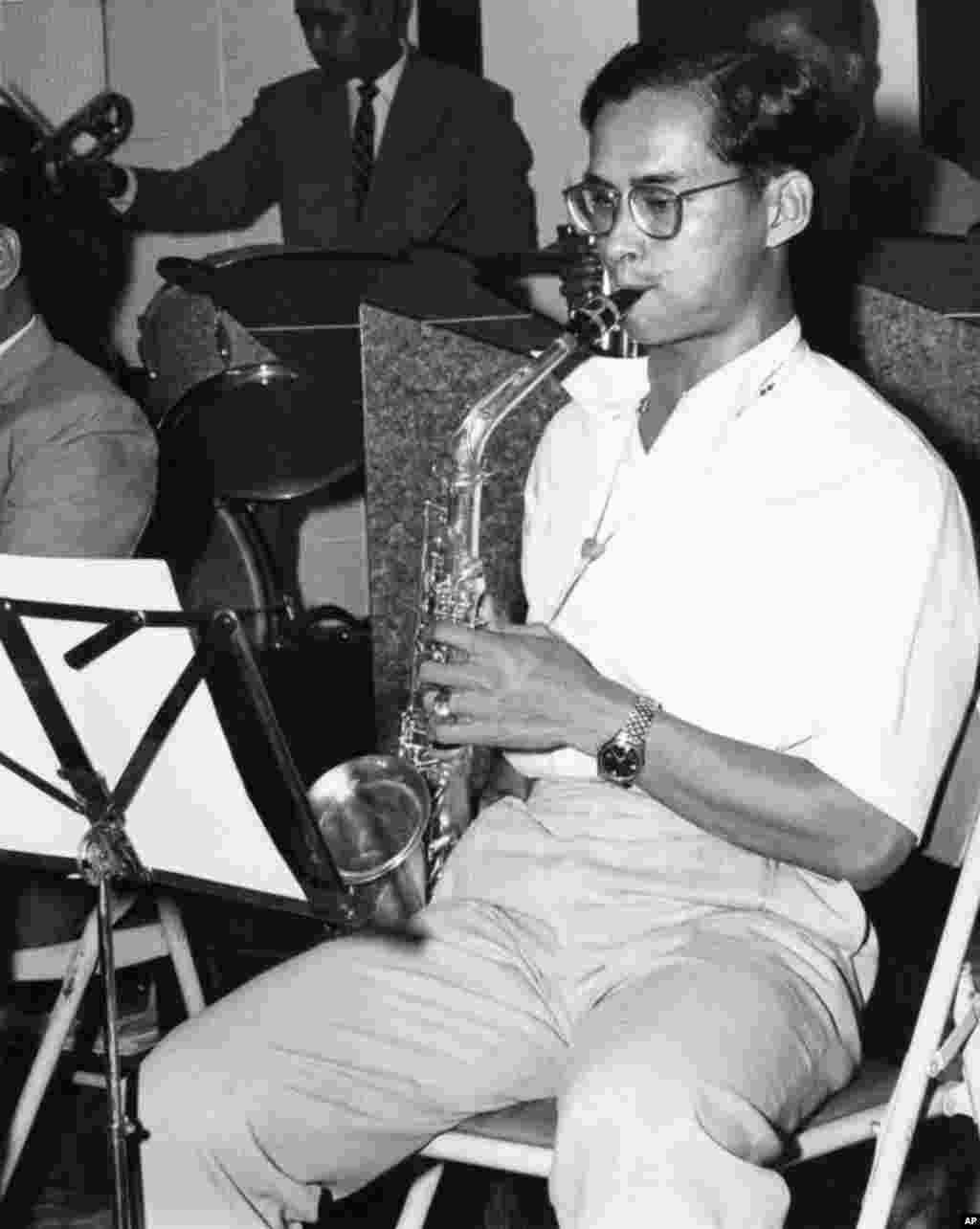 King Bhumibol Adulyadej clad in sports shirt and slacks, swings into a hot chorus on the alto sax with his 13-piece jazz band, Nov. 13, 1962.