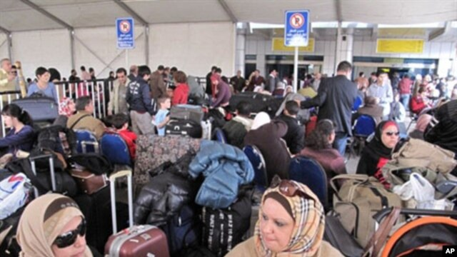 Passengers wait under large tent set-up in the parking lot outside Cairo's International airport as Egyptians and foreigners prepare to leave Egypt, February 01, 2011
