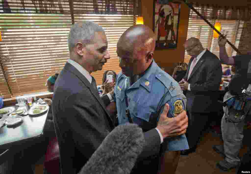 Attorney General Eric Holder greets Capt. Ron Johnson of the Missouri State Highway Patrol at Drake's Place Restaurant in Florrissant, Missouri Aug. 20, 2014.