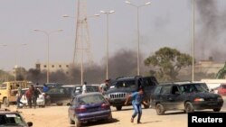 Protesters run after an attack on a Libyan militia, the Libya Shield brigade, headquarters in Benghazi, Jun. 8, 2013.