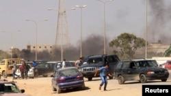 Para demonstran lari menyusul sebuah serangna terhadap milisia Brigade Perisai Libya, di Benghazi (8/6).