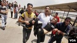 Warga Palestina membawa seorang rekan mereka yang ditembak oleh polisi Israel dalam bentrokan di perbatasan Gaza (15/5).