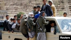 FILE - Houthi fighters ride a patrol truck in Sana'a, Yemen, March 5, 2015. Thousands of the rebels are conducting military exercises near Saudi Arabia, sources say.