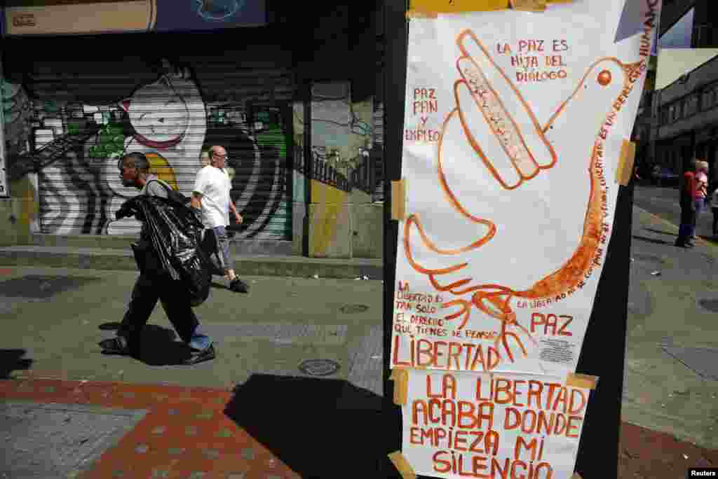 Pedestrians walk past a poster promoting peace at Chacao district in Caracas, February 27, 2014. Unrest sparked by student-led protests against President Nicolas Maduro's socialist government has killed at least 13 people in Venezuela. REUTERS/Tomas B
