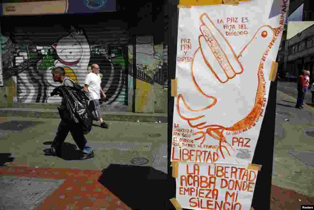 Warga melewati sebuah poster yang mempromosikan perdamaian di daerah Chacao, Caracas (27/2). (Reuters/Tomas Bravo)