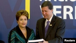 Brazilian President Dilma Rousseff receives the report from Pedro Dallari, a member of the truth commission, in Brasilia, Dec. 10, 2014.