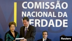 Presiden Brazil Dilma Rousseff (kiri) menerima laporan dari Pedro Dallari, anggota Komisi Kebenaran, di Brasilia (10/12). (Reuters/Joedson Alves)