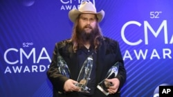 Singer/songwriter Chris Stapleton holds the awards for the male vocalist of the year, song of the year and single of the year at the 52nd annual CMA Awards at Bridgestone Arena, Nov. 14, 2018, in Nashville, Tenn.