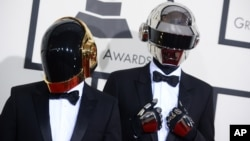 """法国电音二人组合""""蠢朋克""""戴着机器人头盔面具抵达洛杉矶第56届格莱美奖颁奖典礼会场。(2014年2月26日)"""