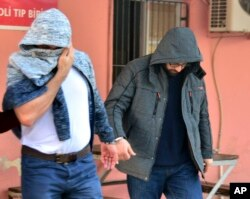 Two men, identified by Turkey's state-run news agency, as Mahamad Laban, 45, right, and Mohammed Tofik Saleh, 38, walk to a police van outside a police station in Adana, Turkey, Feb. 11, 2017. The Anadolu news agency said that the arrested men were suspected of receiving Islamic State group weapons and explosives training in Syria for the past three months and of planning attacks in Europe.