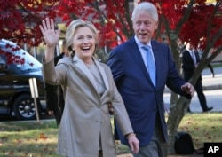 FILE - Then-Democratic presidential candidate Hillary Clinton and her husband, former President Bill Clinton, greet supporters after voting in Chappaqua, N.Y., Nov. 8, 2016.
